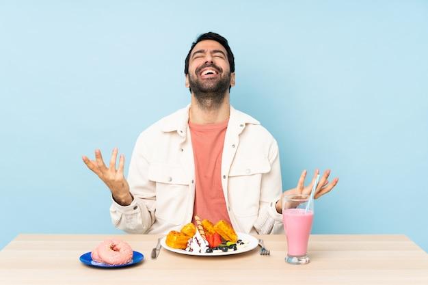 Homme, table, avoir, petit déjeuner, gaufres, milkshake, sourire, beaucoup