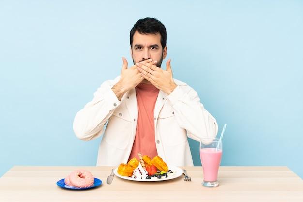 Homme à une table ayant des gaufres pour le petit déjeuner et un milkshake couvrant la bouche avec les mains