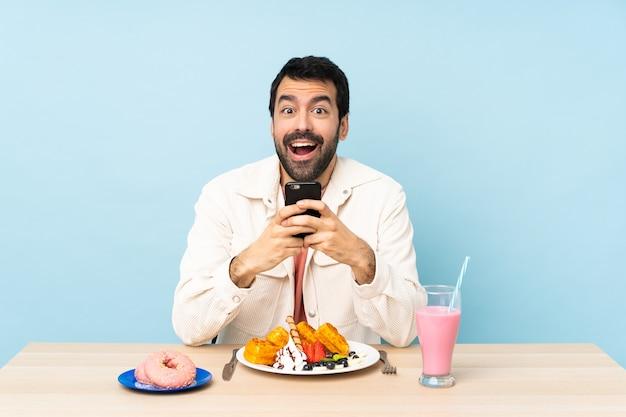 Homme à une table prenant le petit déjeuner des gaufres et un milk-shake surpris et envoyant un message