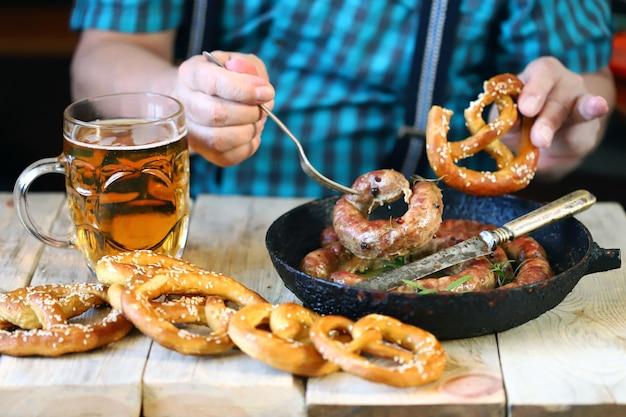 Un homme à table avec un verre de bière, un bretzel et une poêle avec des saucisses. célébration de l'oktoberfest.