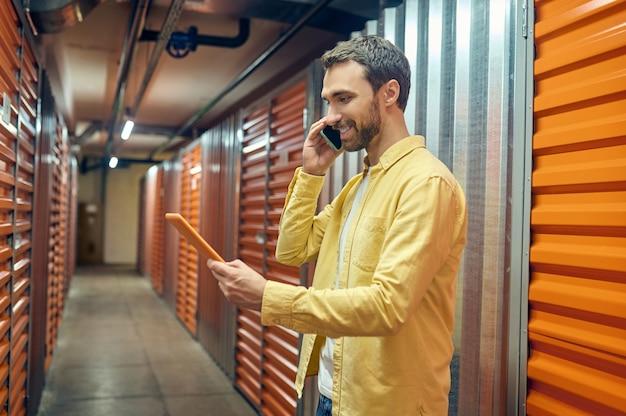 Homme avec tablette parlant sur smartphone