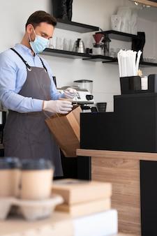 Homme avec tablier préparant des plats à emporter
