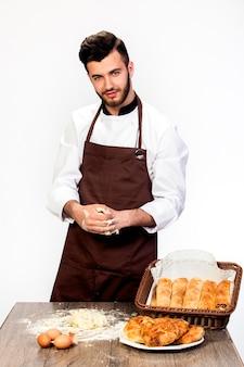 Un homme en tablier prépare la pâte pour la cuisson, modèle cook sur un espace blanc pétrit la pâte sur la table décorée de produits de boulangerie