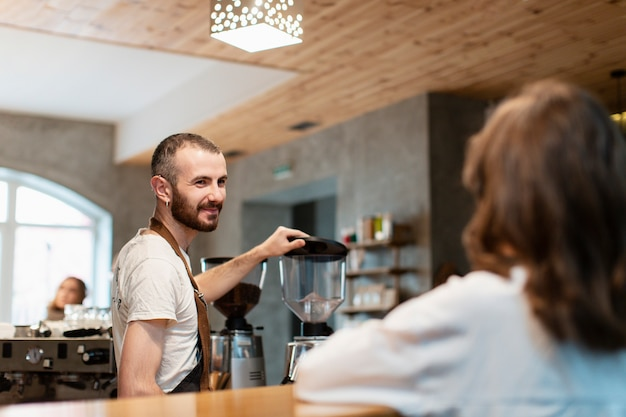 Homme en tablier souriant et café