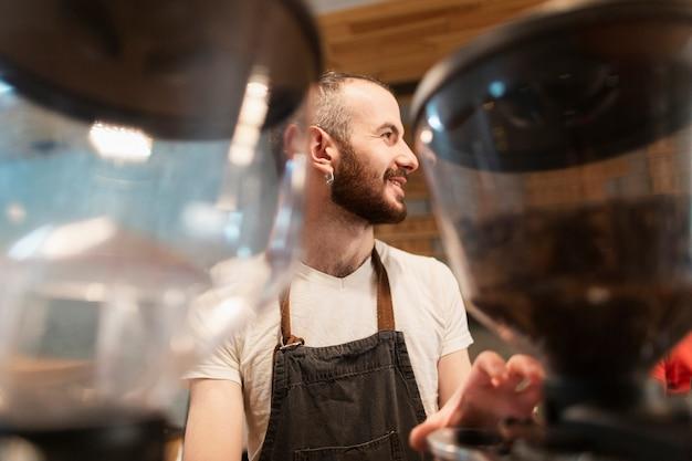 Homme avec tablier travaillant et porte-café défocalisé