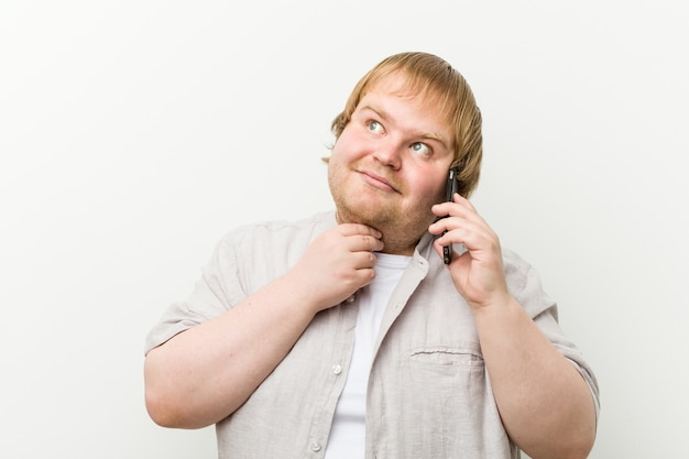 Homme de taille plus caucasien appelant par téléphone à côté avec une expression douteuse et sceptique.