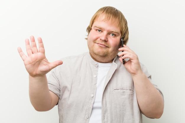 Homme de taille plus caucasien appelant par téléphone debout avec la main tendue montrant le panneau d'arrêt, vous empêchant.