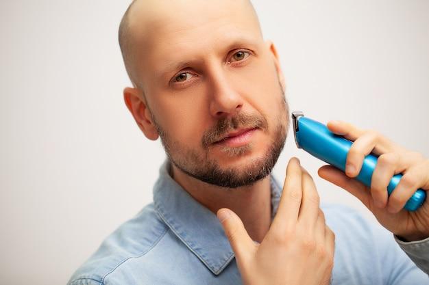 L'homme taille sa barbe avec une machine à écrire électrique