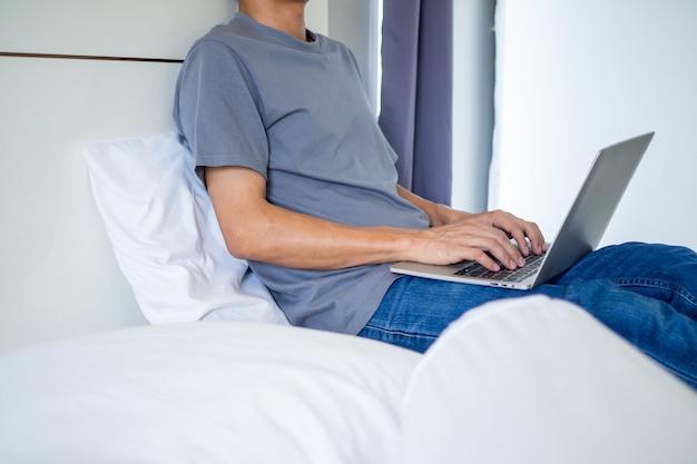 Homme tapant ou chat social à l'aide d'un ordinateur sur le lit dans la chambre.