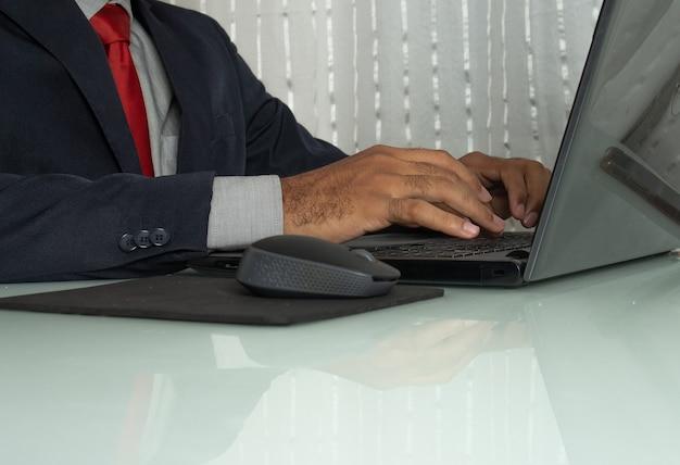 Homme tapant dans un ordinateur près de la souris sous la table blanche au bureau