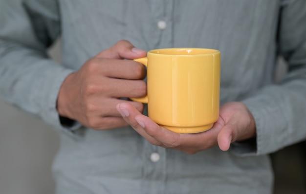 Homme avec une tasse de café jaune à la main
