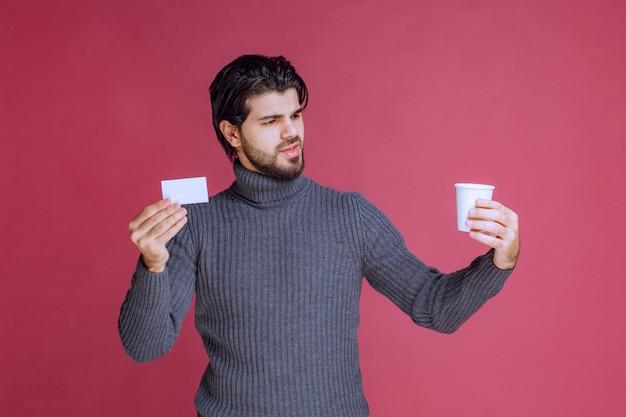 Homme avec une tasse de café montrant sa facture ou sa carte de visite.