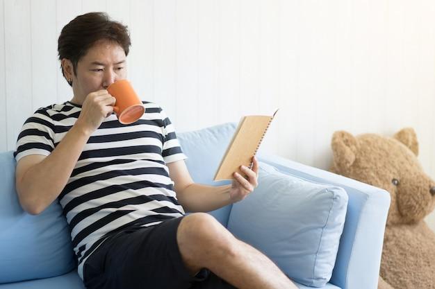 Homme avec une tasse et lire un livre pour se détendre dans le salon à la maison