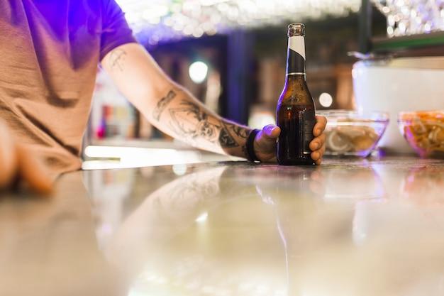 Homme tatouage, tenue, bouteille alcool, sur, table réfléchissante