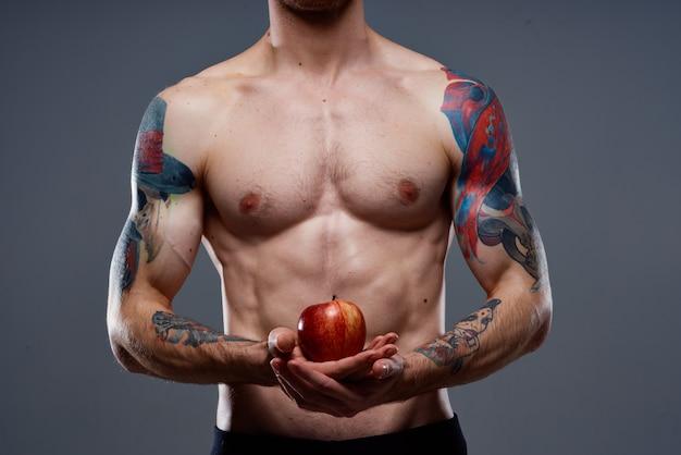 Homme avec un tatouage tient une pomme dans ses mains torse nu muscles pompés biceps presse