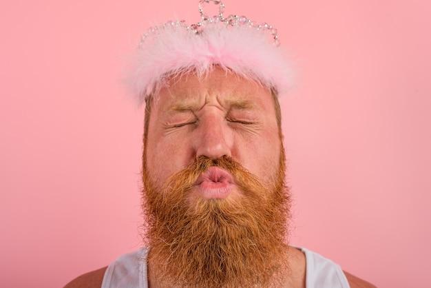 L'homme avec des tatouages de barbe et une couronne agit comme une princesse
