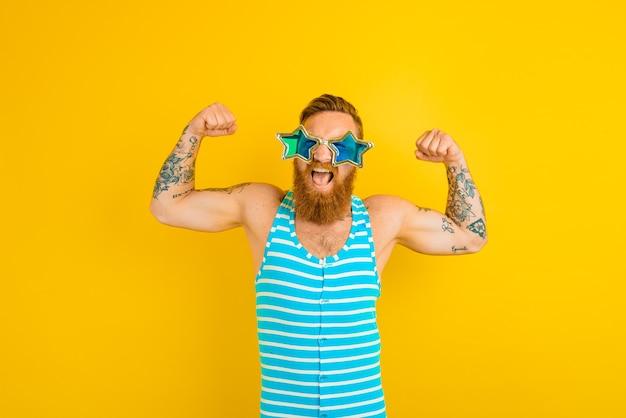 L'homme avec des tatouages de barbe et un maillot de bain montre ses muscles