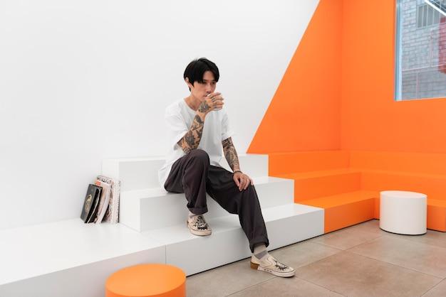 Homme avec des tatouages buvant du café au café