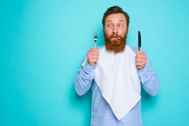 L'homme avec des tatouages est prêt à manger avec des couverts à disposition