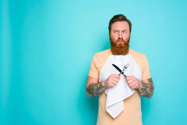 L'homme avec des tatouages est prêt à manger avec des couverts à la main avec un certain doute