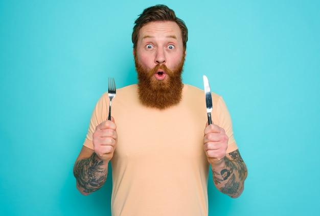 L'homme avec des tatouages est prêt à manger quelque chose avec des couverts à disposition
