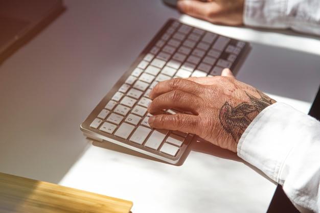 Homme avec des tatouages sur internet sur ordinateur portable à la table de bureau