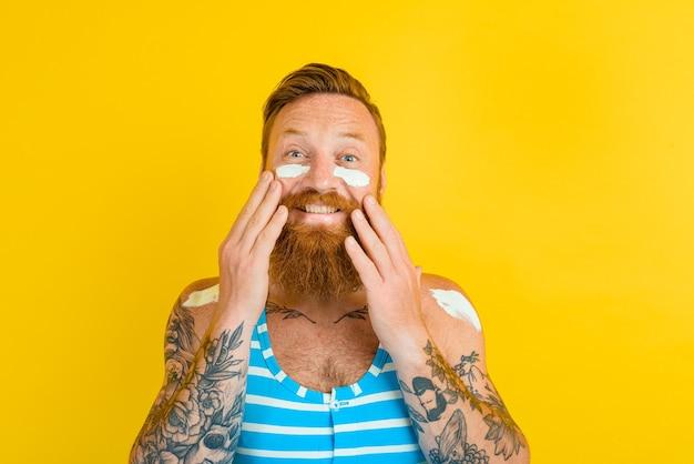 Un homme avec des tatouages et un maillot de bain met de la crème solaire