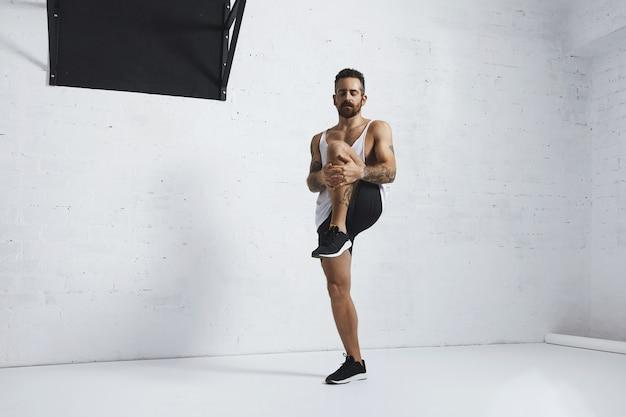 Homme tatoué athlétique en t-shirt réservoir blanc blanc faisant des genoux, étirant ses jambes avec les yeux fermés