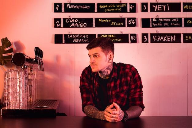Homme tatoué en attente dans un bar