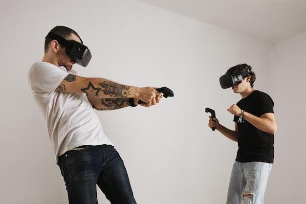 Un homme tatoué barbu vêtu d'un t-shirt blanc frappe un jeune homme vêtu d'un t-shirt noir dans un jeu en réalité virtuelle