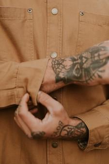 Homme tatoué boutonnant sa chemise brune en gros plan