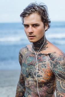 Homme tatoué avec un casque contre le ciel bleu sur l'océan