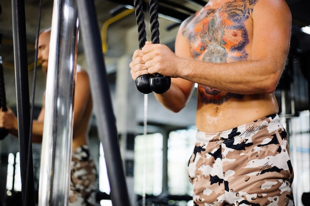 Homme tatoué faisant de l'exercice à la salle de sport