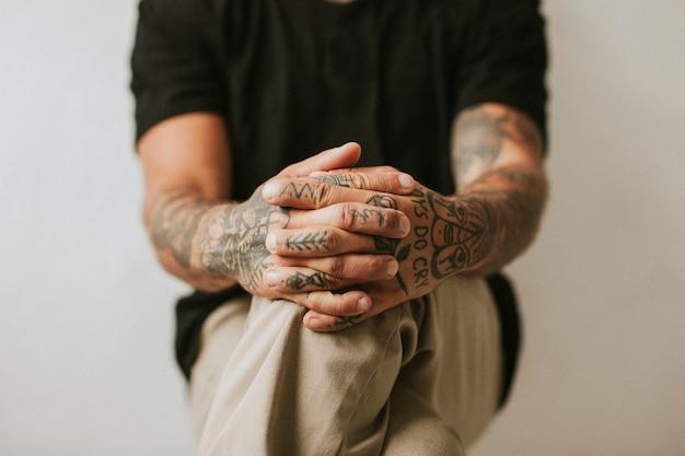 Homme tatoué avec les mains joignant ses genoux