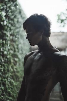 Homme tatoué posant contre la pluie
