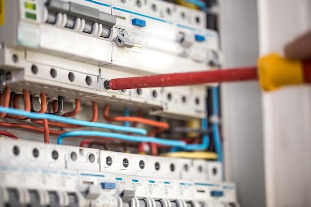 Homme, technicien électricien travaillant dans un tableau avec fusibles. installation et connexion d'équipements électriques. fermer.