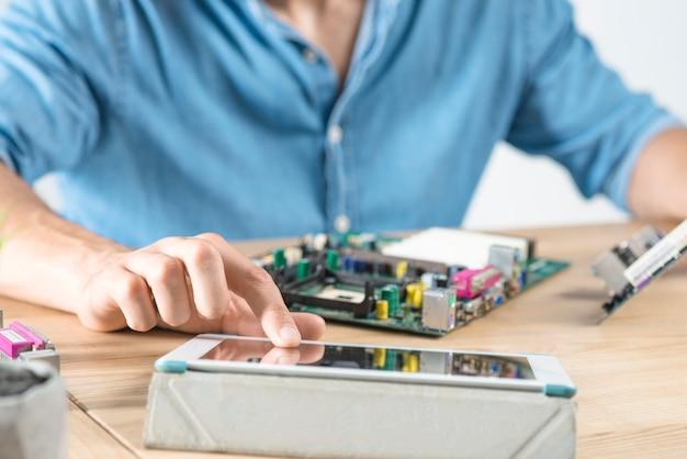Homme technicien touchant l'écran de la tablette numérique travaillant sur l'équipement matériel