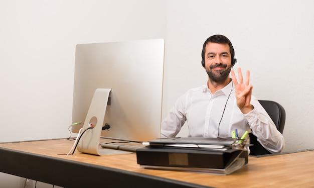 Homme de télémarketer dans un bureau heureux et comptant trois avec les doigts