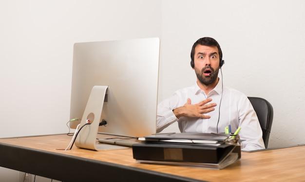 Homme de télémarketer dans un bureau surpris et choqué en regardant à droite