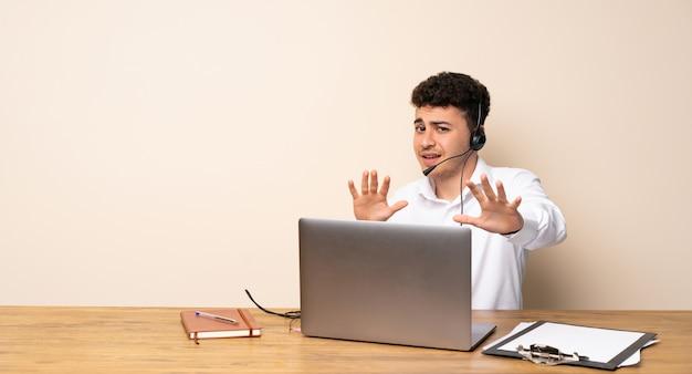 Homme de télémarketing nerveux qui s'étend de mains à l'avant