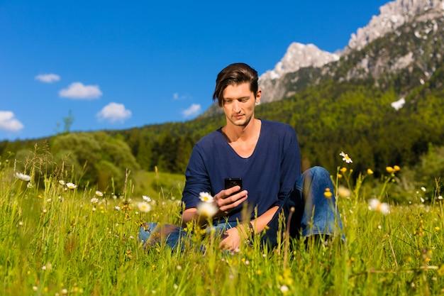 Homme avec téléphone assis dans les montagnes