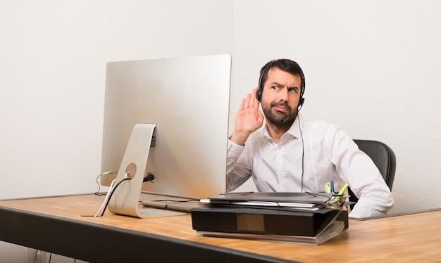 Homme de téléphone dans un bureau écoutant quelque chose en mettant la main sur l'oreille
