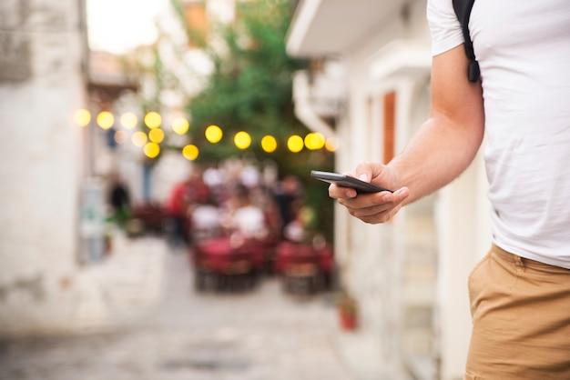 Homme avec un téléphone intelligent à portée de main, fond flou