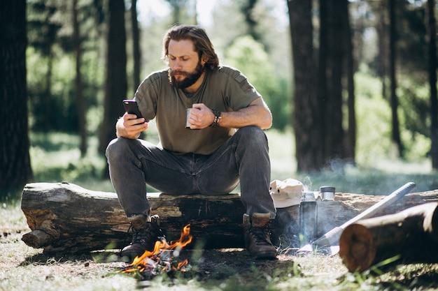 Homme avec un téléphone par feu de joie dans la forêt