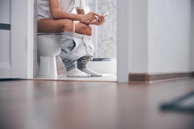 Homme avec un téléphone portable assis sur le siège des toilettes
