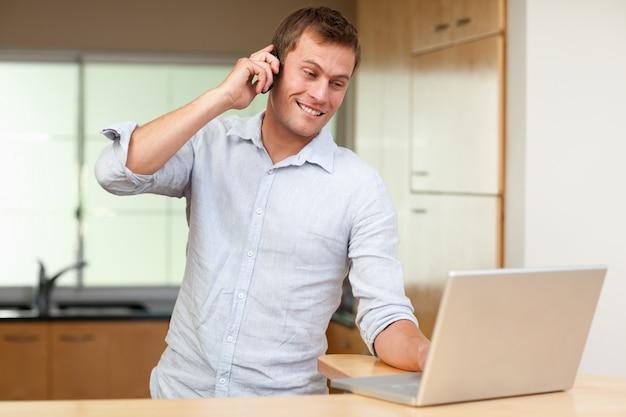 Homme avec téléphone portable et ordinateur portable dans la cuisine