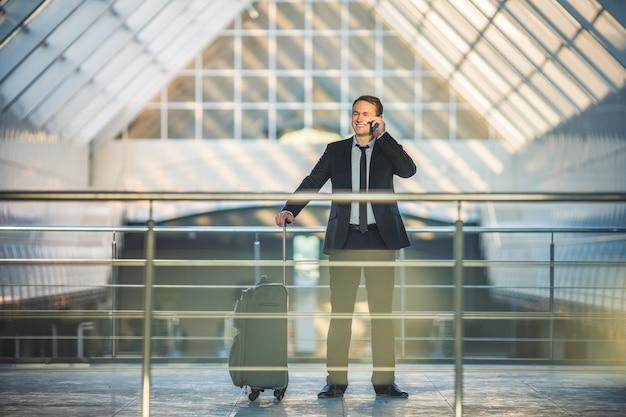 L'homme avec un téléphone de valise dans le centre d'affaires