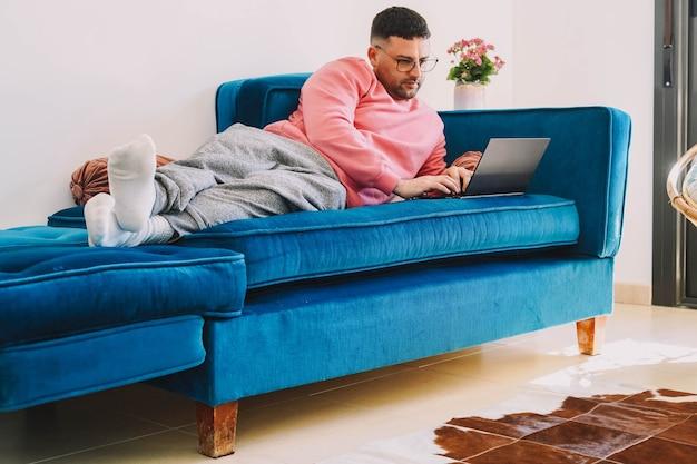 Homme télétravaillant depuis le canapé à la maison avec l'ordinateur en raison de la pandémie de coronavirus