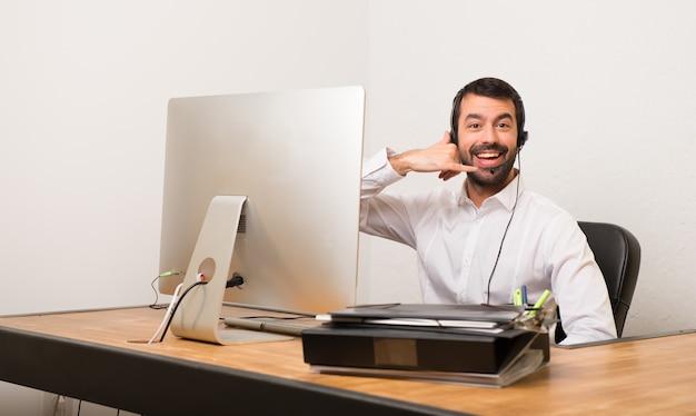 Homme de télévendeur dans un bureau en faisant un geste de téléphone. rappelle-moi
