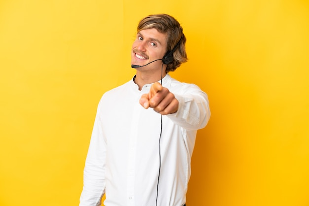 Homme de télévendeur travaillant avec un casque isolé sur un mur jaune pointant vers l'avant avec une expression heureuse